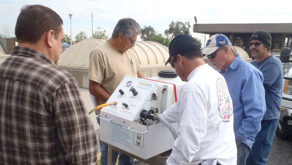 group of people training on a Medora Corporation disinfectant boost system for potable water storage tanks