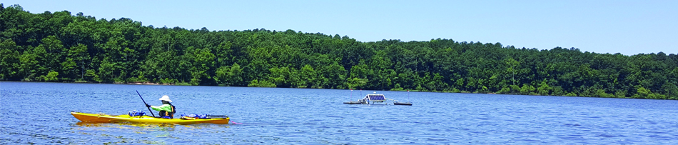 canoe passing by SolarBee during Jordan Lake SolarBee Demonstration Project