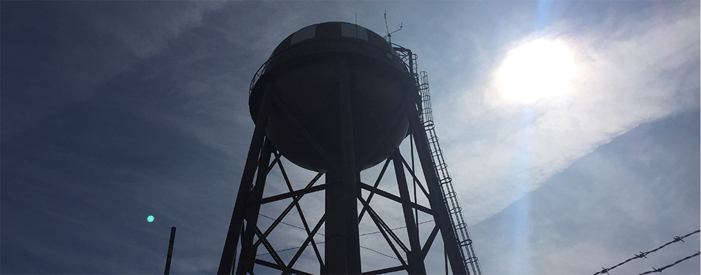 potable water storage tank with blue sky and sun