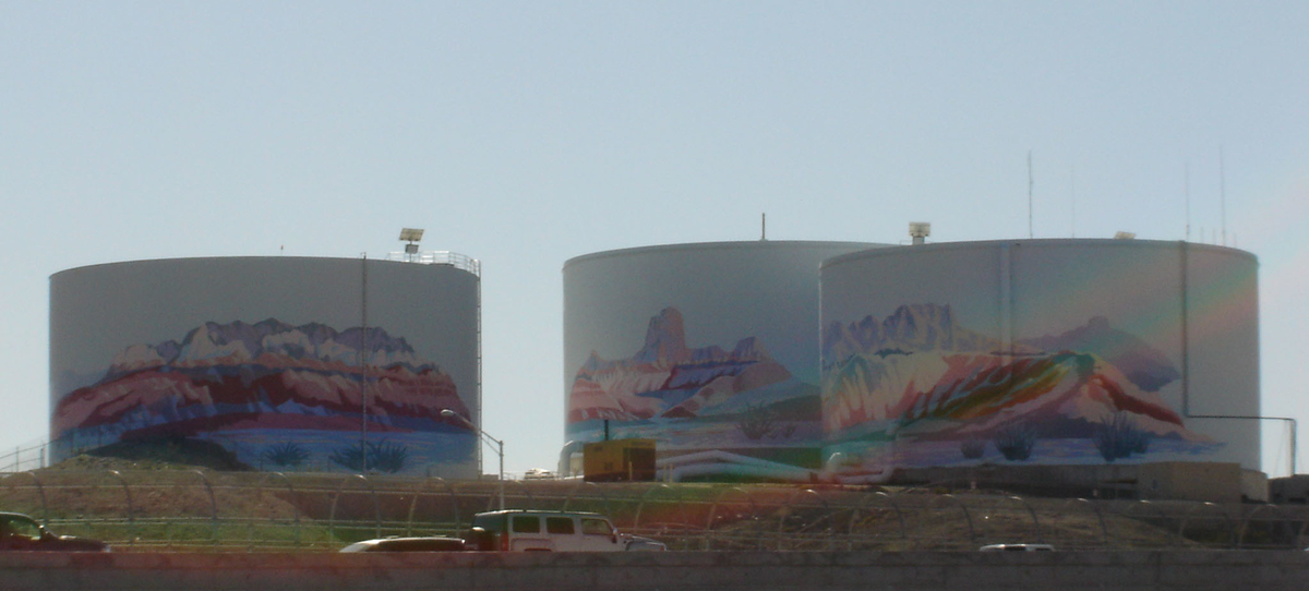 nicely painted water storage tanks in distance road traffic in foreground