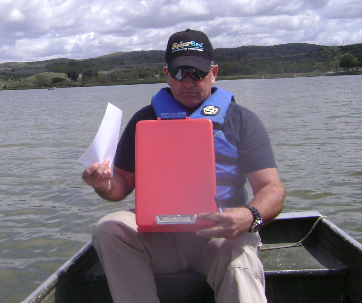 in a boat on a lake reviewing water quality test data